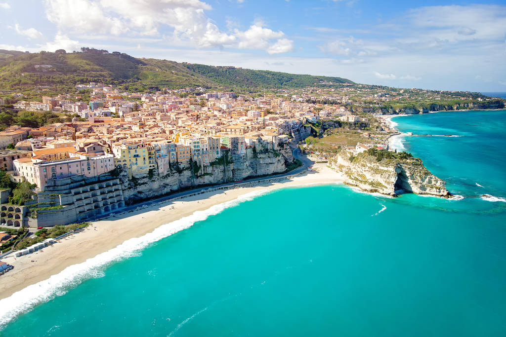 City of Tropea, tourist destination in Calabria, Italy. Aerial view of city, monastery and coastline from Drone