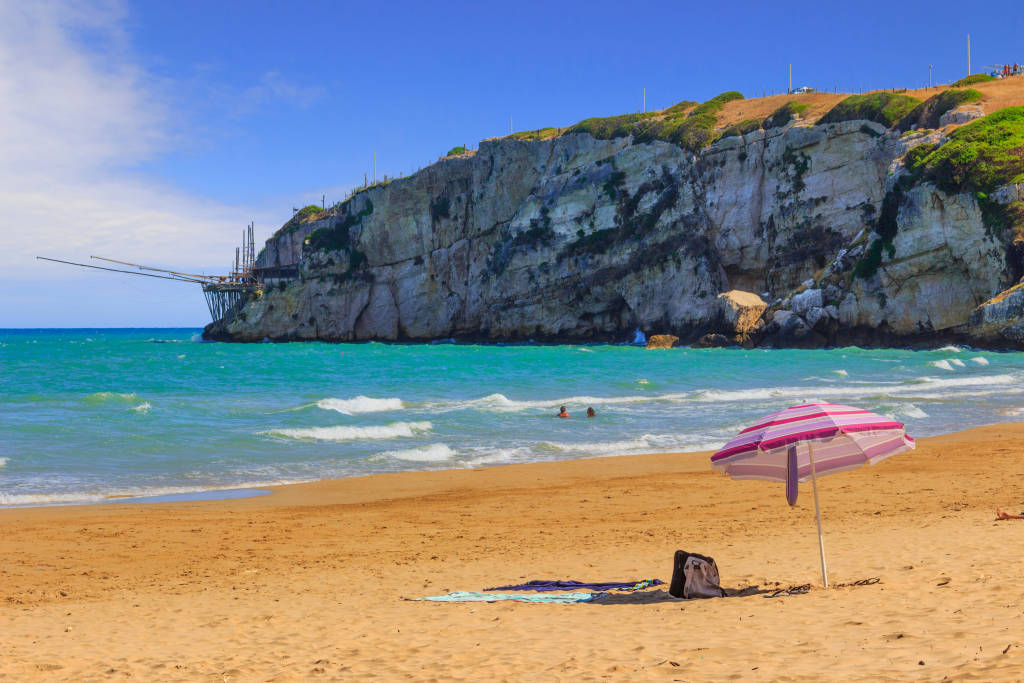 The most beautiful beaches of Apulia: Zaiana Bay, enclosed by two rocks, stretches a few kilometres away from Peschici in Gargano, Italy. In the background a characteristic trabucco (or trebuchet).
