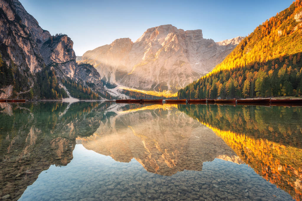 Beautiful Braies lake at sunrise in autumn in Dolomites, Italy. Landscape with mountains, yellow sunlight, water with reflection, trees with orange leaves in fall. Travel in italian alps. Nature
