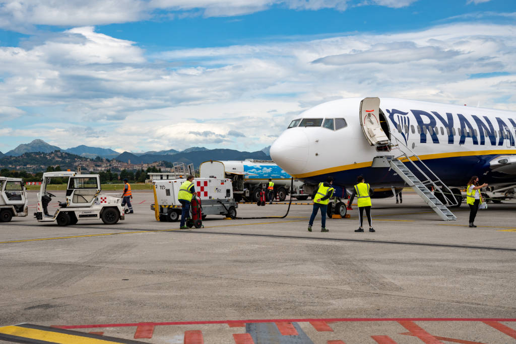 """Bergamo, Italy - 4th August, 2020: Refueling of a Ryanair plane at Orio al Serio airport before passengers board and skyline of """"Città alta"""" further in the background."""