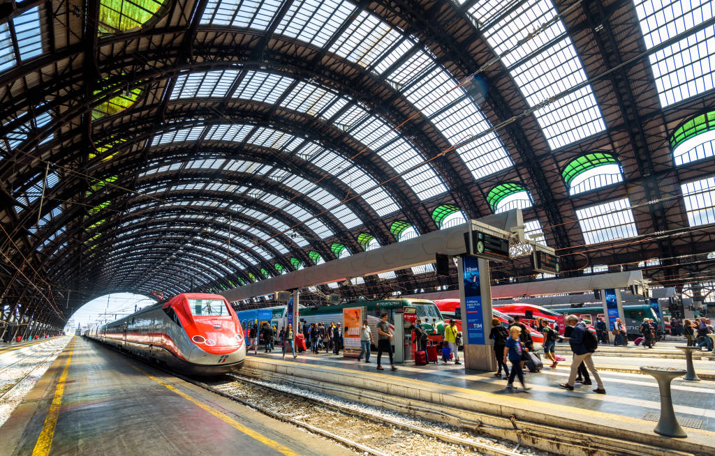 Milan, Italy - May 17, 2017: People and high-speed trains at the railway Milan Central Station. Panorama of industrial landmark of Milan. Concept of travel and transport across Milan and Europe.