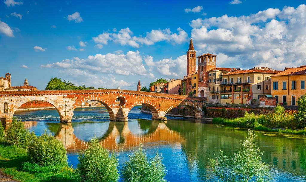 Panoramiczny widok na most Ponte Pietra w Weronie na rzece Adige. Region Veneto. Włochy. Słoneczny letni dzień panorama i błękitne dramatyczne niebo z chmurami. Starożytne europejskie włoskie terakoty kolor domów
