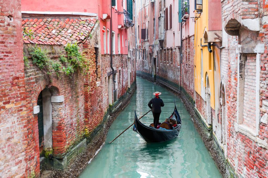 Venetian gondolier punting gondola przez zielone wody kanału Wenecji Włochy