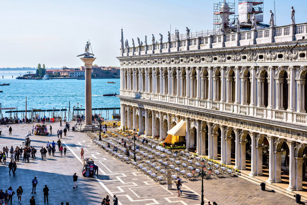 VENICE, ITALY - APRIL 03, 2017: Daylight view to Marciana Library facade and Columns of San Marco and San Todaro from Saint Mark's square. Tourists walking on street. Venetian Lagoon on background.