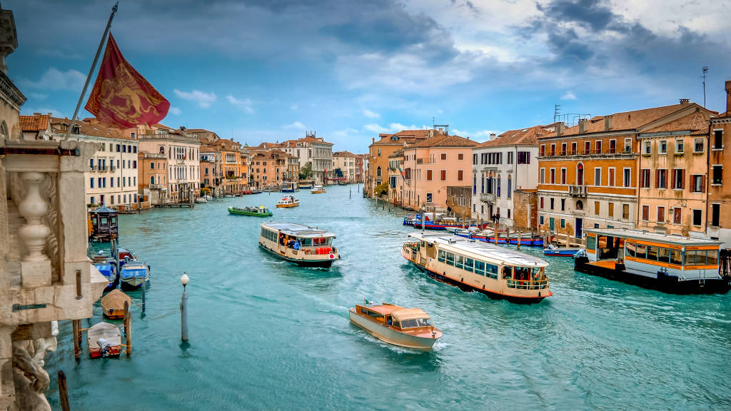 Water taxi and vaporetto boats traverse the Grand Canal in Venice, Italy, faces and logos blurred for commercial use