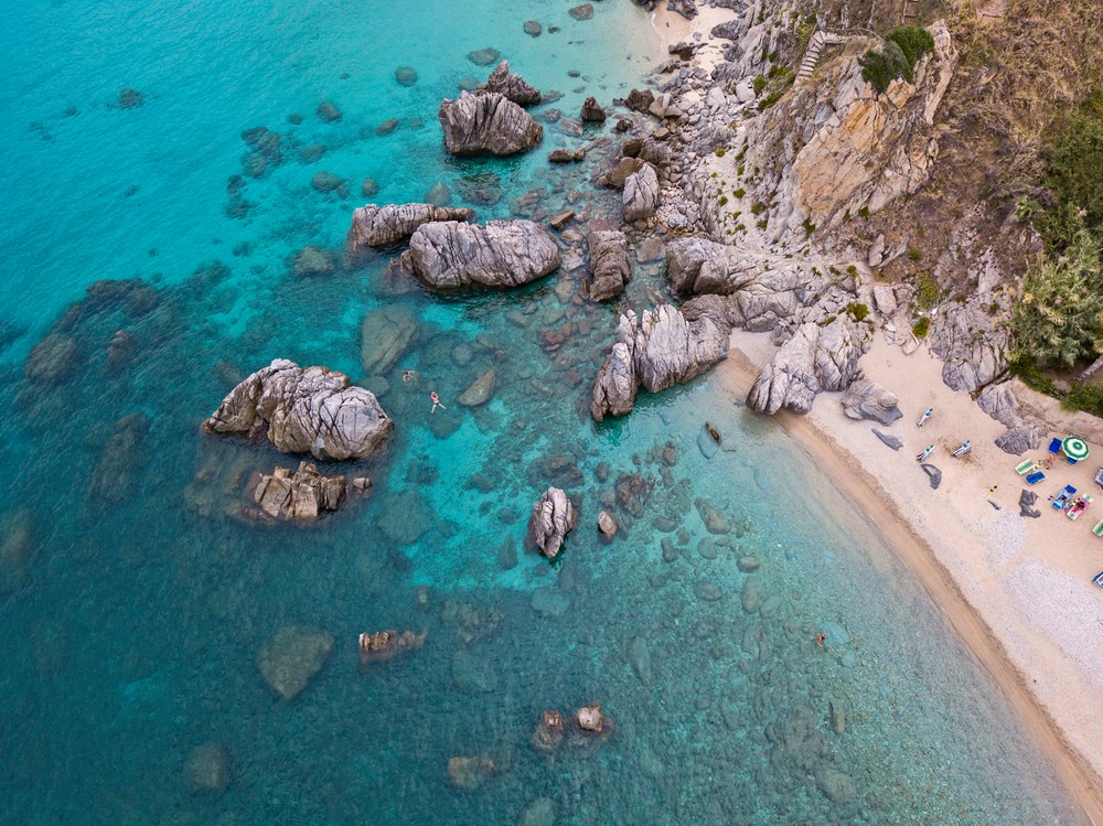 Aerial view of a beach and umbrellas. Tropea, Calabria, Italy.  Parghelia. Overview of seabed seen from above, transparent water. Swimmers, bathers floating on the water. Beach and rocks of Vardanello