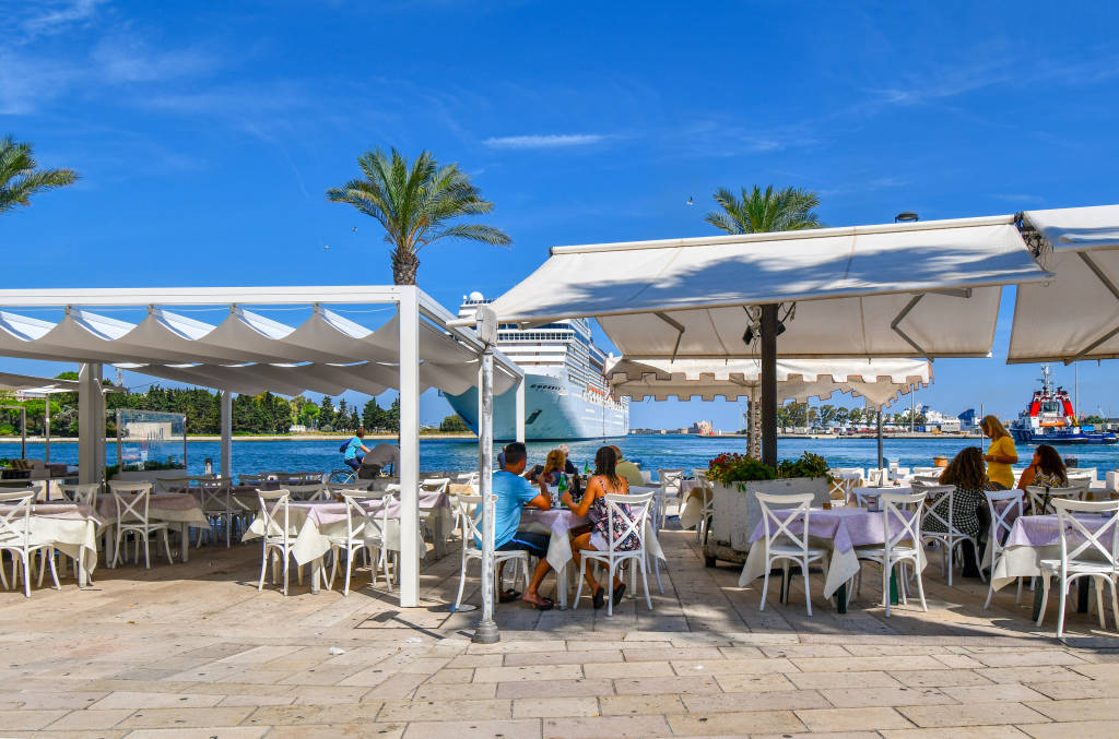 Brindisi, Italy - September 20 2018: Tourists enjoy a waterfront afternoon meal on the Brindisi, Italy promenade as a large cruise ship prepares to dock on a summer day in the Puglia region of Italy.