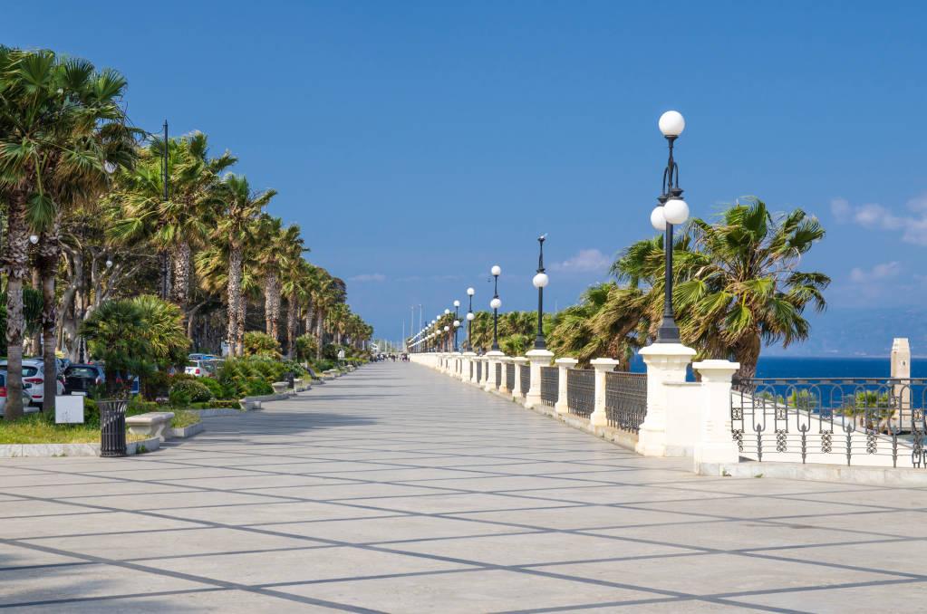 Reggio di Calabria quay waterfront promenade Lungomare Falcomata with view of Strait of Messina connected Mediterranean and Tyrrhenian sea and Sicily island background, Southern Italy