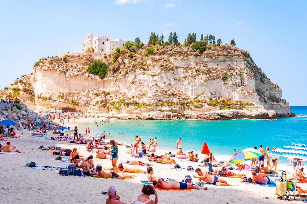 Rotonda Beach, Tropea, Calabria, Italy - September 07, 2019: Landscape view on famous Rotonda Beach full of resting sunbathing and swimming people. Sanctuary Santa Maria on the peak of a massive cliff