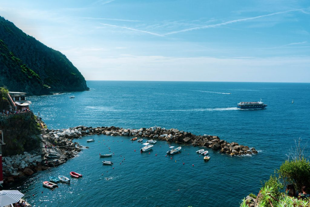 The sea view from the Cinque Terre. The boats sail between the waters and the rocks. A small house overlooking the sea colors the view.