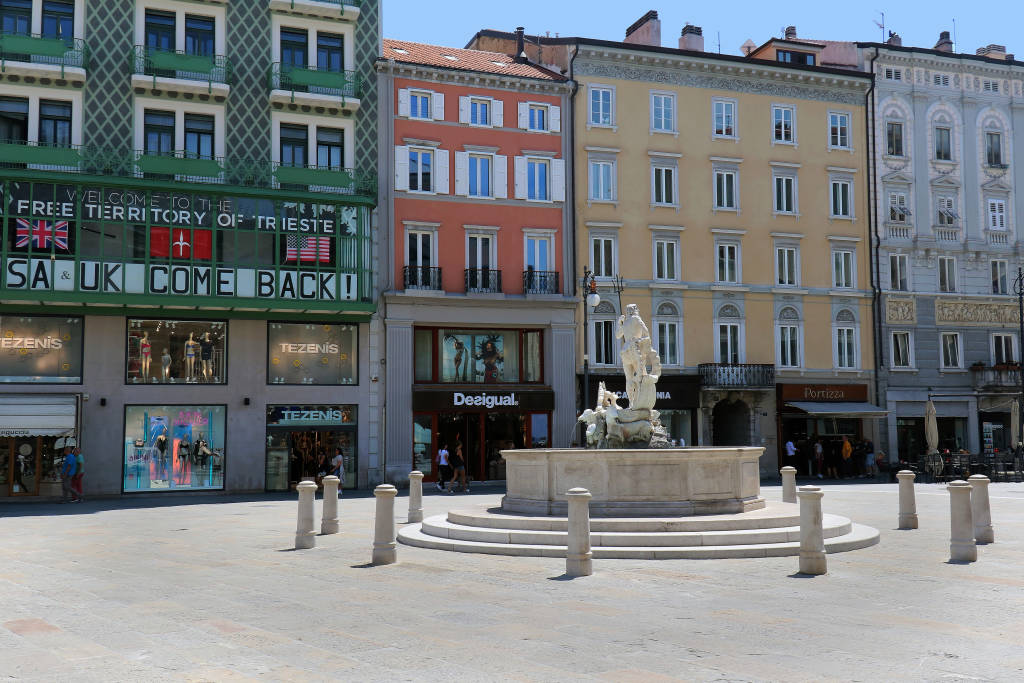 Trieste, Italy - June 17, 2019: Ancient fountain of Neptune in Piazza della Borsa in Trieste with shops in street background