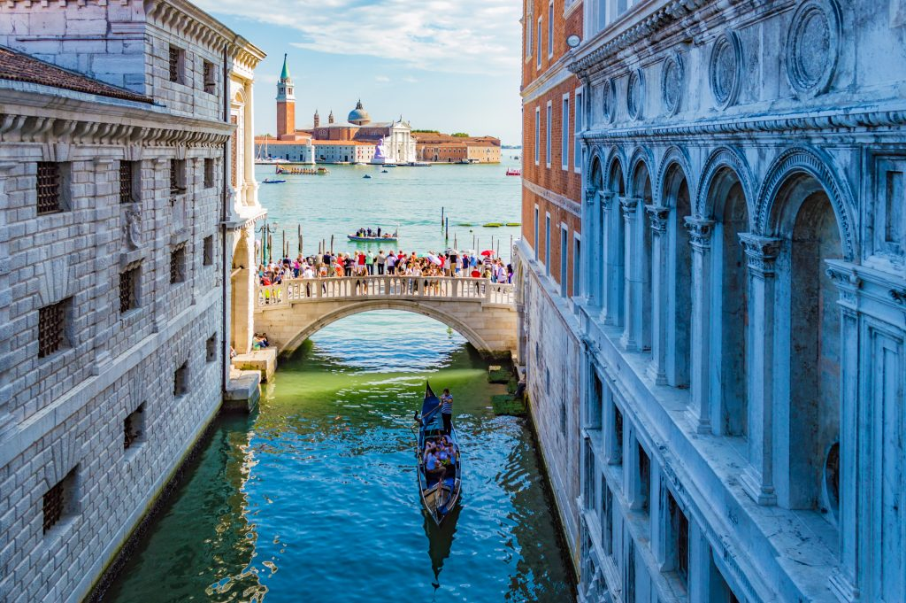 Venice, Italy - CIRCA 2013: Venice scenery: A narrow canal Rio del Palazzo; with the bridge Ponte della Paglia at its end; and the Church San Giorgio Maggiore at the background.