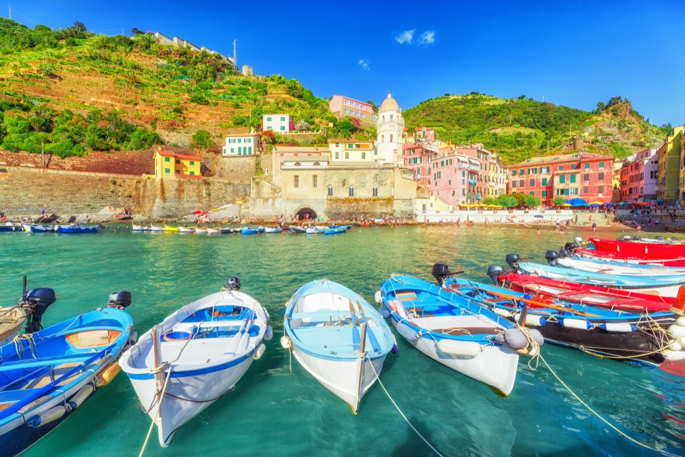 Vernazza village in Cinque Terre National park, Italy. Coastline landscape with colorful wooden fishing boats and beautiful medieval architecture of Vernazza town in background. UNESCO heritage site.