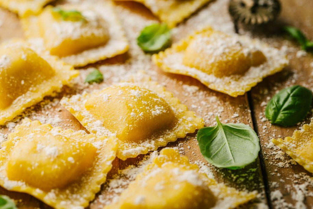 Tasty raw ravioli with flour and basil on wooden background. Process of making italian ravioli. Closeup