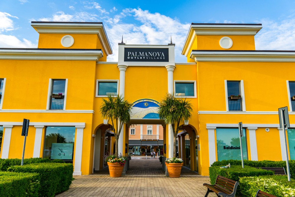 PALMANOVA, ITALY - MAY 23, 2019: Entrance at Palmanova Outlet Village in Italy. Village was opened in 2008 and hosts over 90 retailers.