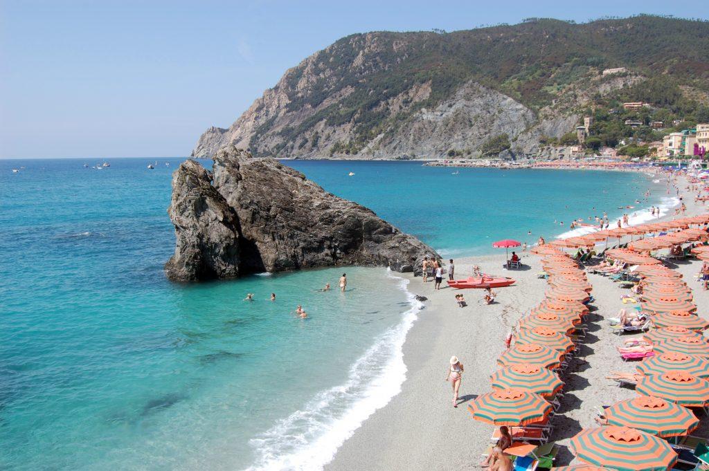 rows of orange  stripped beach umbrellas on a private beach in Monterosso al Mare,  Cinque Terre, Italy