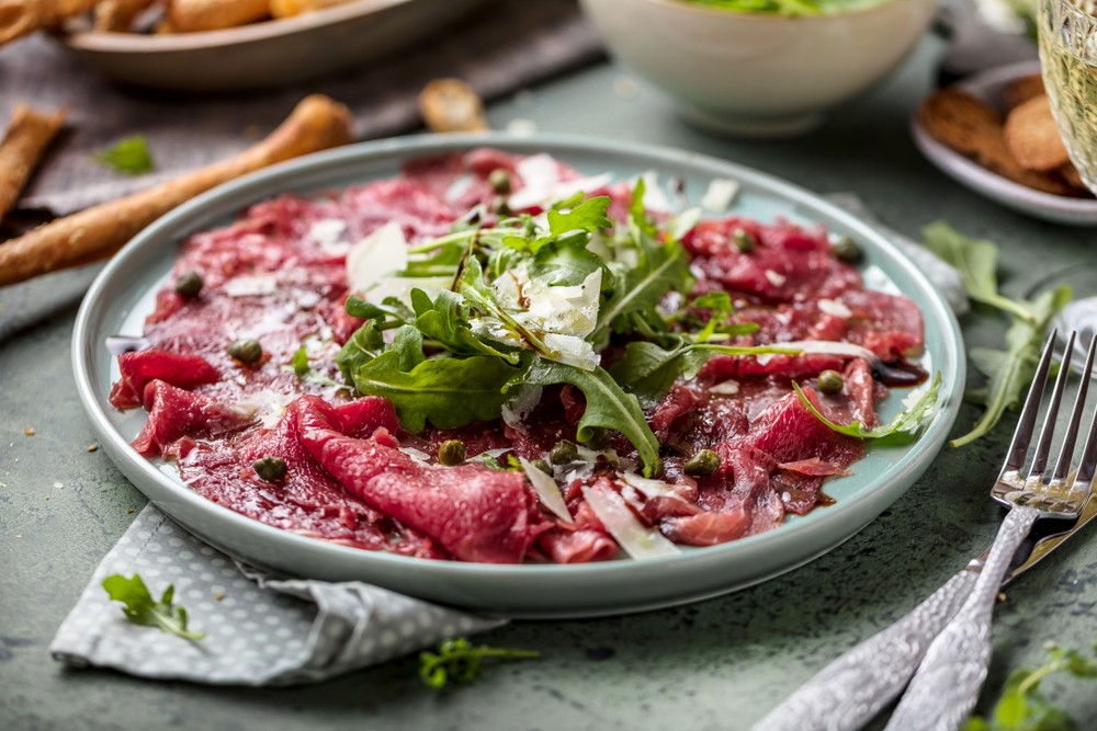 Beef,Carpaccio,On,Black,Plate,With,Mustard,And,Parmesan