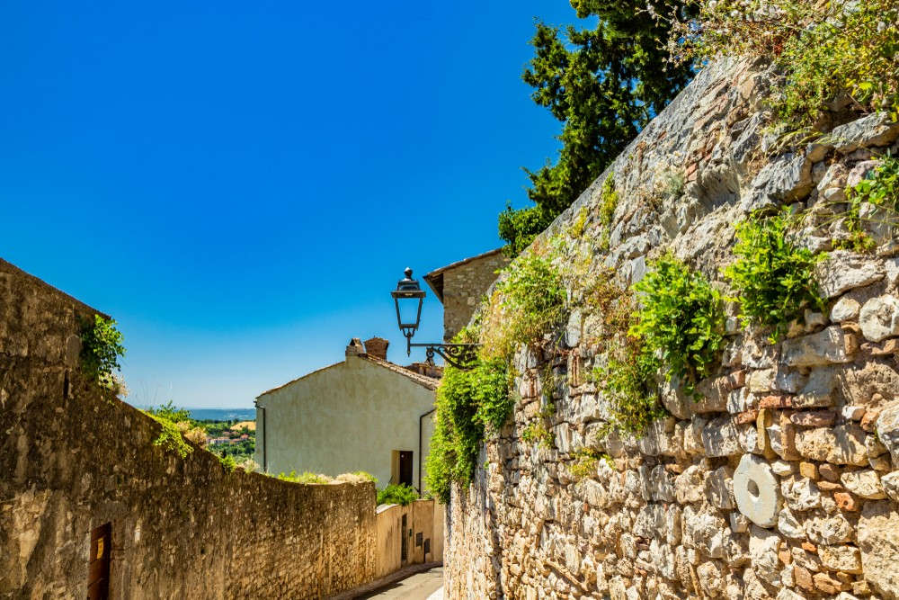 A narrow alley in the city of Amelia, in Umbria. Weeds grow on the large stone wall. The street in perspective, an old iron street lamp.