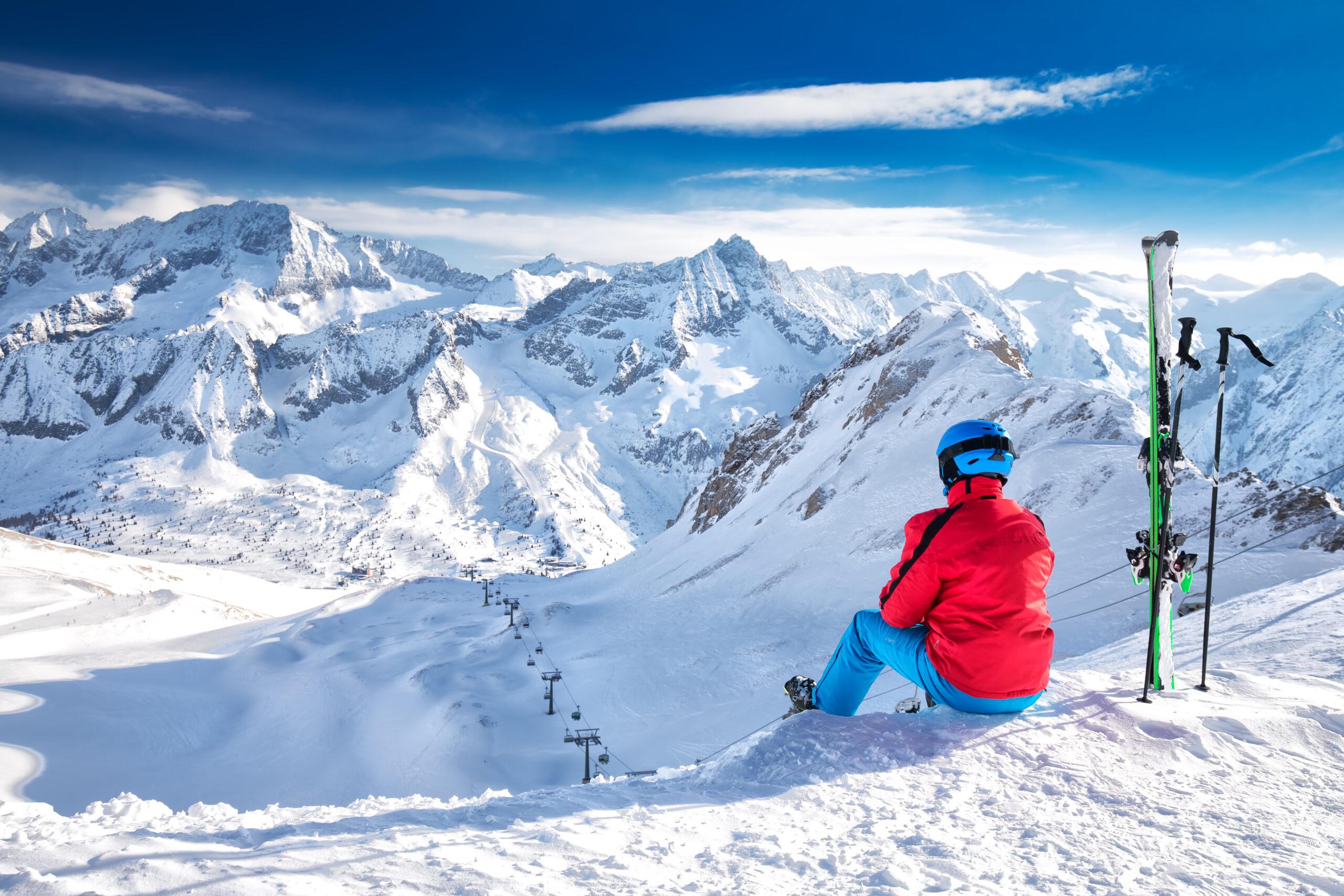 Młody, szczęśliwy narciarz siedzący na szczycie góry i podziwiający widok na Alpy Retyckie, przełęcz Tonale, Włochy, Europa. , licencja: shutterstock/By Eva Bocek