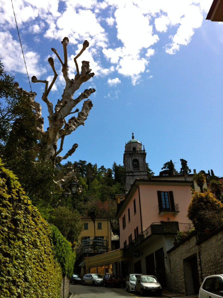 BELLAGIO, ITALY – APRIL 22, 2012: a street, bulidings, and the top part of the Bell tower of Basilica of St. James (San Giacomo)church at Bellagio, a town located on Lake Como, Lombardy Region