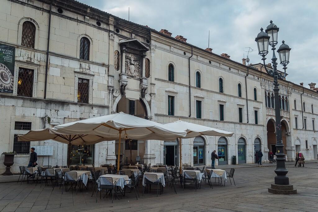 Brescia, Italy - December, 2015: Main square in Brescia. Piazza della Loggia with street cafe in Brescia. Beautiful lantern near empty sidewalk restaurant with opened umbrellas in the center Brescia.