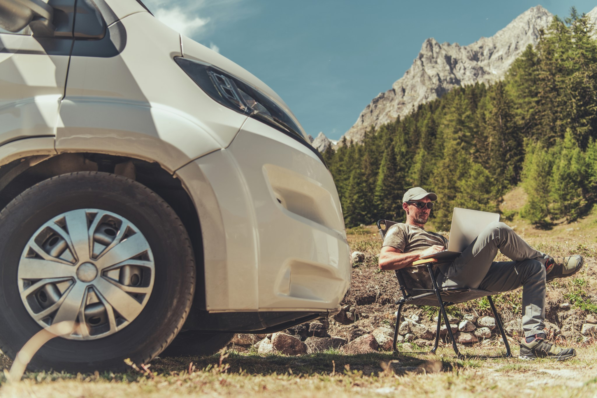 Caucasian Men with Modern Laptop Computer in His Hands Working Remotely While Camping in RV Camper Van Motorhome. High Mountains Landscape in a Background. Work and Travel Theme.