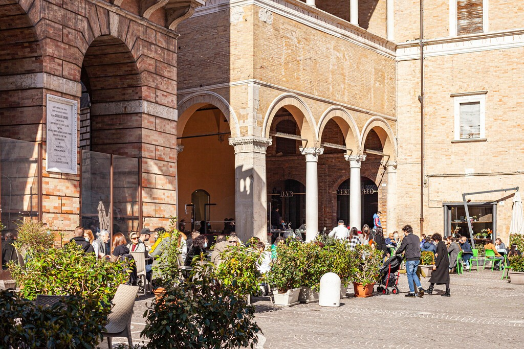Macerata, Italy - February 21, 2021: People enjoying sunny day and outdoor and resting in the restaurant, wolking on the street.