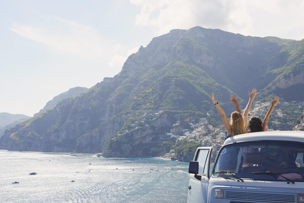 Piękna szczęśliwa dziewczyna turystyczna przyjaciele ciesząc się malowniczym widokiem ramiona podniesione z wybrzeża Amalfi na lato podróż przygodowa wakacje w vintage van