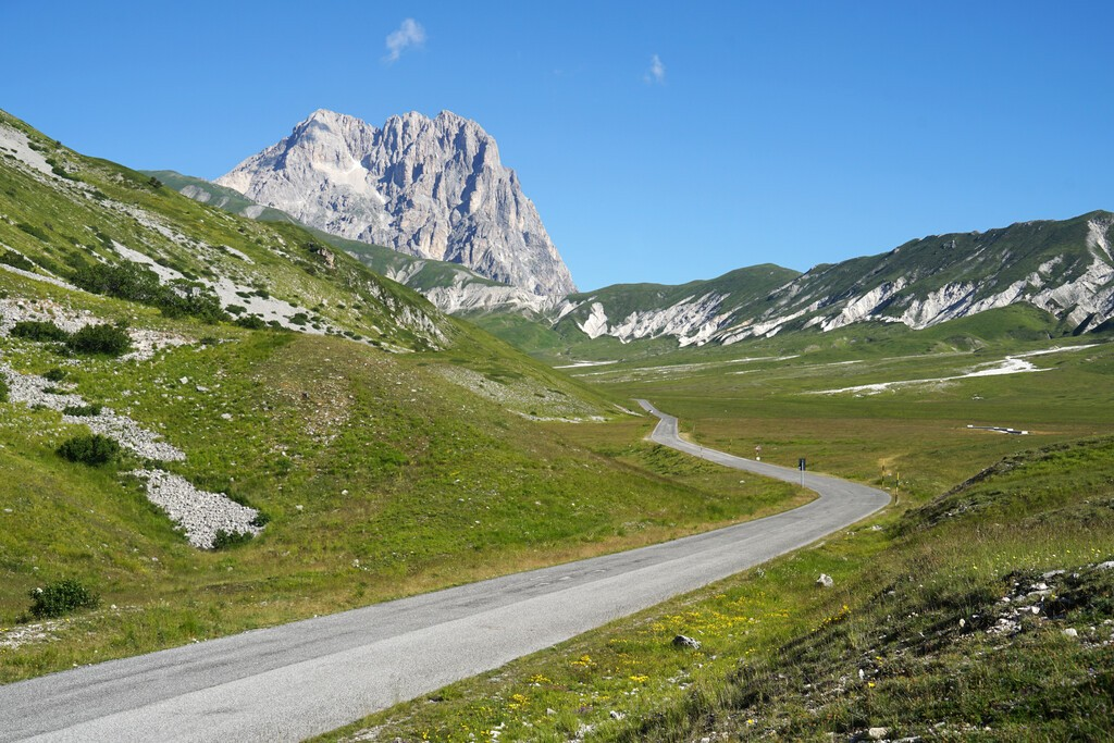 Road to Corno Grande Mountain, highest mountain of Apennine Mountains with grassy landscape, Gran Sasso National Park, Abruzzo, Italy, travel and climbing concept