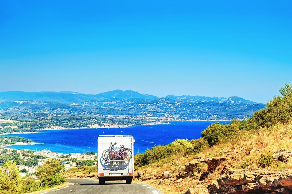 RV Camper Van Car with bicycles on Road. Caravan and motorhome in the road trip  in Provence, Azure Coast, France. In front of the sea and mountains.