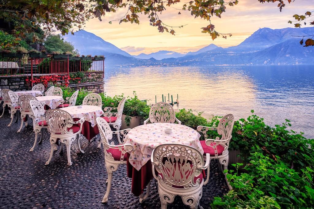 Stoły w małej kawiarni na nabrzeżu jeziora Como, Włochy, z panoramą Alp w tle na zachodzie słońca