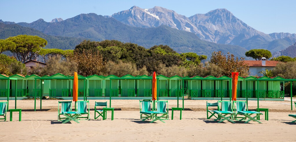 The beach of Forte dei Marmi at the beginning of the season, the beach umbrellas are still closed, in the background the Apuan Alps