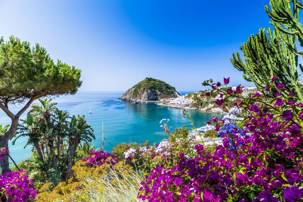Widok Sant'Angelo na wyspie Ischia we Włoszech: Morze Tyrreńskie, glabra bougenvillea, skały, woda, parasol, piasek i typowe domy na wyspie przed Neapolem, Kampania w słoneczny dzień